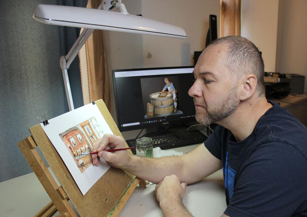 Der Illustrationskünstler Sascha Lunyakov bei der Fertigstellung des Aquarelldioramas.